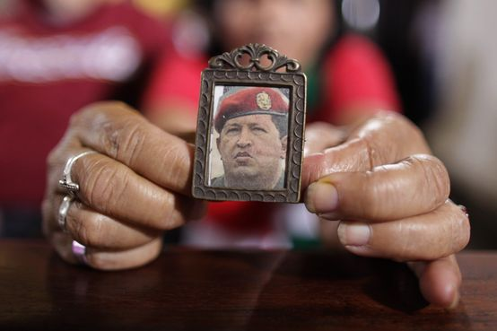 A woman holds an image of Venezuela's President Hugo Chavez as people